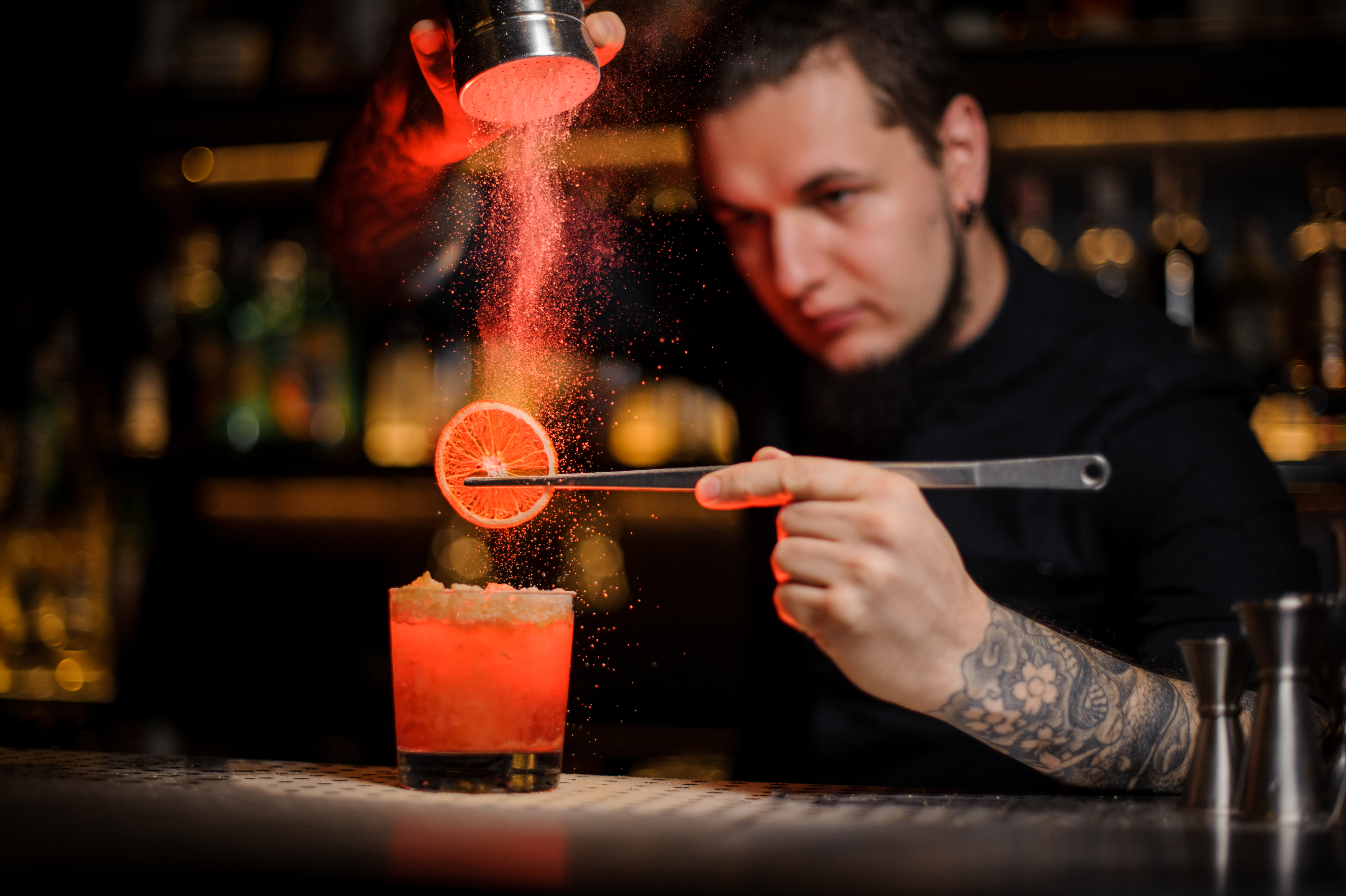 A bartender puts the finishing touches on a drink.